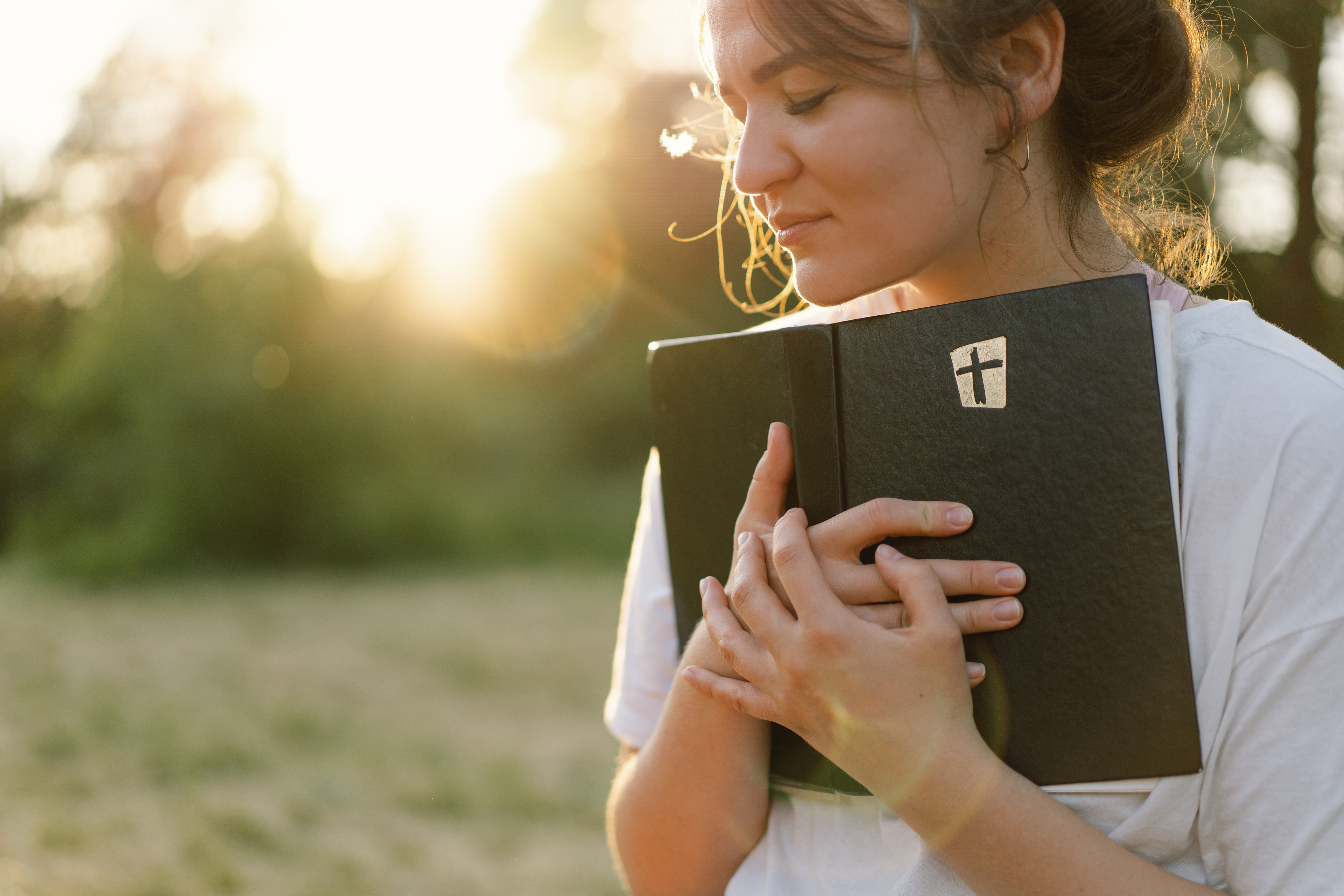 christian-woman-holds-bible-in-her-hands-LHB7X8C image