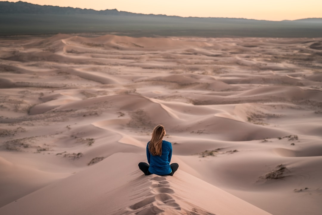 woman-sitting-on-sand-dunes