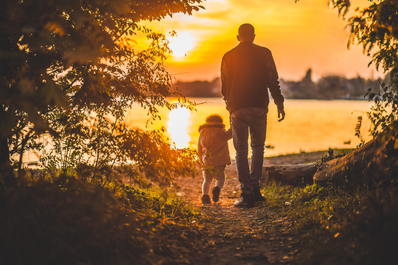 father-and-child-walking-at-sunset