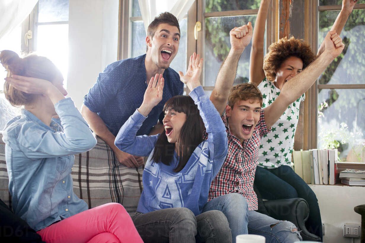 group-of-friends-watching-tv-cheering-CUF43050 image