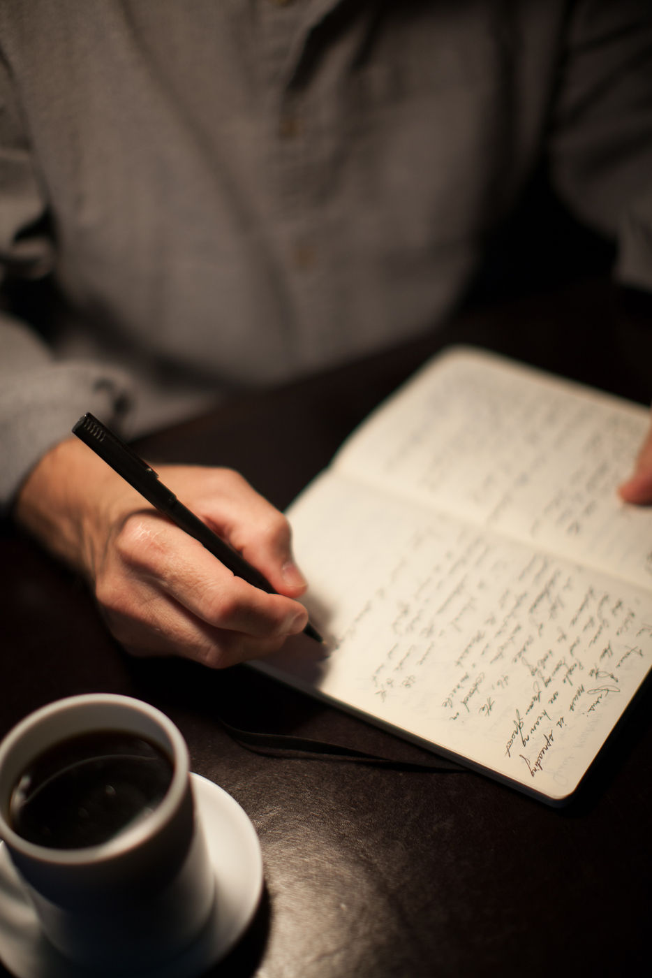 man writing in journal (stock photo)